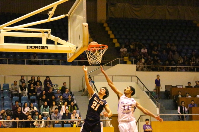 Raeden Richardson '17, small forward on the Yale-NUS basketball team, goes up for a lay up against NYU Shanghai.